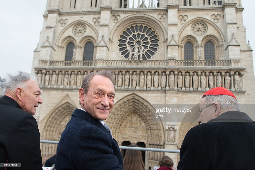 Paris' mayor Bertrand Delanoe (C) looks on next to Patrick Jacquin (L), the head priest and rector of the Notre-Dame de Paris cathedral, and French archbishop Andre Vingt-Trois (R), prior to the ringing of the new bells of Notre Dame Cathedral in Paris on March 23, 2013, as part of the formal inauguration.
