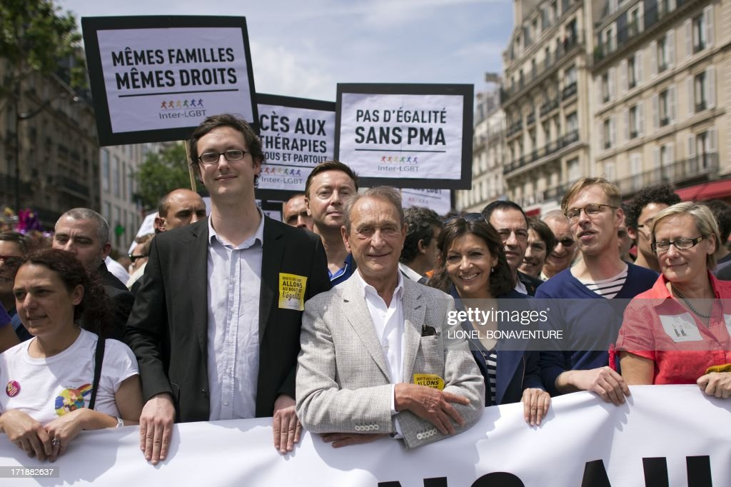 Paris mayor Bertrand Delanoe (C) parades with Paris deputy mayor Anne Hidalgo (3rdR) during the homosexual, lesbian, bisexual and transgender (HLBT) visibility march, the Gay Pride, on June 29, 2013 in Paris, exactly one month after France celebrated its first gay marriage. Sign (L) reads: 'Same families, same rights' and sign (C) reads: 'No equality without Assisted Medical Procreation (PMA in French)'.