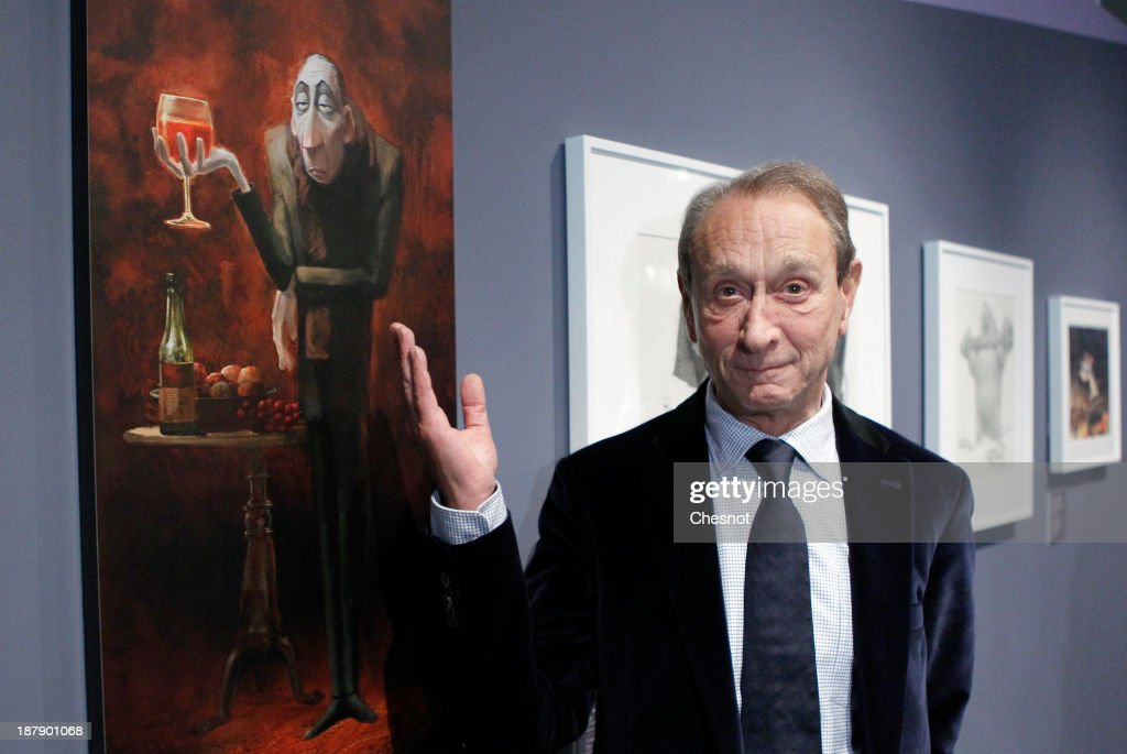 Paris mayor Bertrand Delanoe poses front of a painting of Pixar's film 'Ratatouille' during the inauguration of the exhibition 'PIXAR, 25 Years of Animation' at The Art Ludique Museum on November 13, 2013 in Paris, France.The Art Ludique Museum, the first museum in the world dedicated to the art of entertainment, will open its doors in Paris on November 16 with this exhibition inaugurated at the MoMA in New York in 2006.