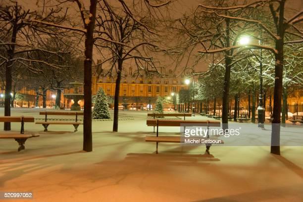 Paris place des Vosges under the snow at night