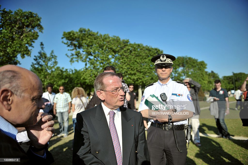 Paris police prefect Michel Gaudin (C) and Paris deputy Jean-Marie Le Guen (L) discuss in the Champs de Mars park where a giant outdoor 'drinks-party' (aperitif in French) organised via Facebook is due to be held on May 23, 2010 in Paris. Propelled by Facebook, a series of such gatherings have been gaining momentum over recent months, with thousands of people turning up for drinks in usually quiet cities like Rennes, Brest and Clermont-Ferrand.