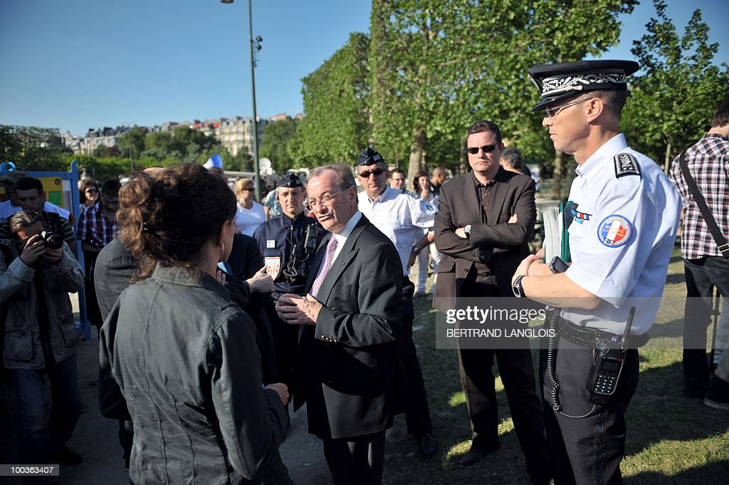 Paris' police prefect Michel Gaudin (C) speaks to an unidentified person in the Champs de Mars park where a giant outdoor 'drinks-party' (aperitif in French) organised via Facebook is due to be held on May 23, 2010 in Paris. Propelled by Facebook, a series of such gatherings have been gaining momentum over recent months, with thousands of people turning up for drinks in usually quiet cities like Rennes, Brest and Clermont-Ferrand.