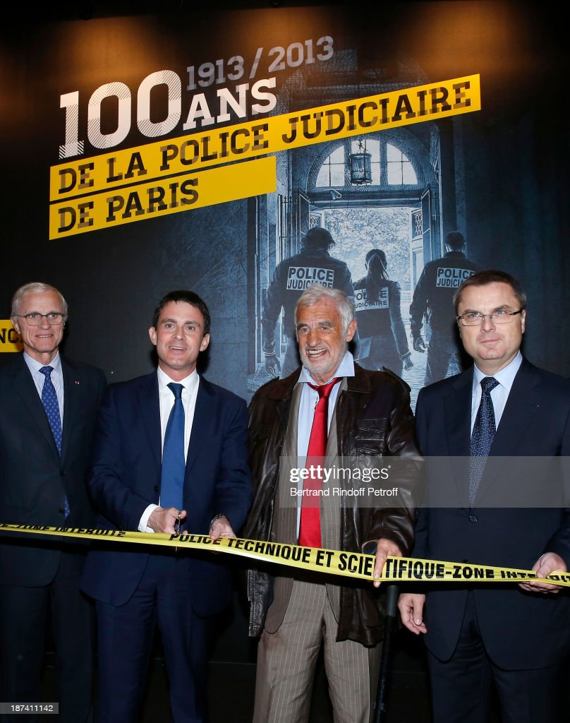 Paris Prefect Bernard Boucault, French Interior Minister <a gi-track='captionPersonalityLinkClicked' href=/galleries/search?phrase=Manuel+Valls&family=editorial&specificpeople=2178864 ng-click='$event.stopPropagation()'>Manuel Valls</a>, cutting the opening ribbon, legendary actor <a gi-track='captionPersonalityLinkClicked' href=/galleries/search?phrase=Jean-Paul+Belmondo&family=editorial&specificpeople=207029 ng-click='$event.stopPropagation()'>Jean-Paul Belmondo</a> and head of the Paris Judicial Police Christian Flaesch attend the '100th Anniversary Of The Paris Judiciary Police' exhibition opening on November 8, 2013 in Paris, France.