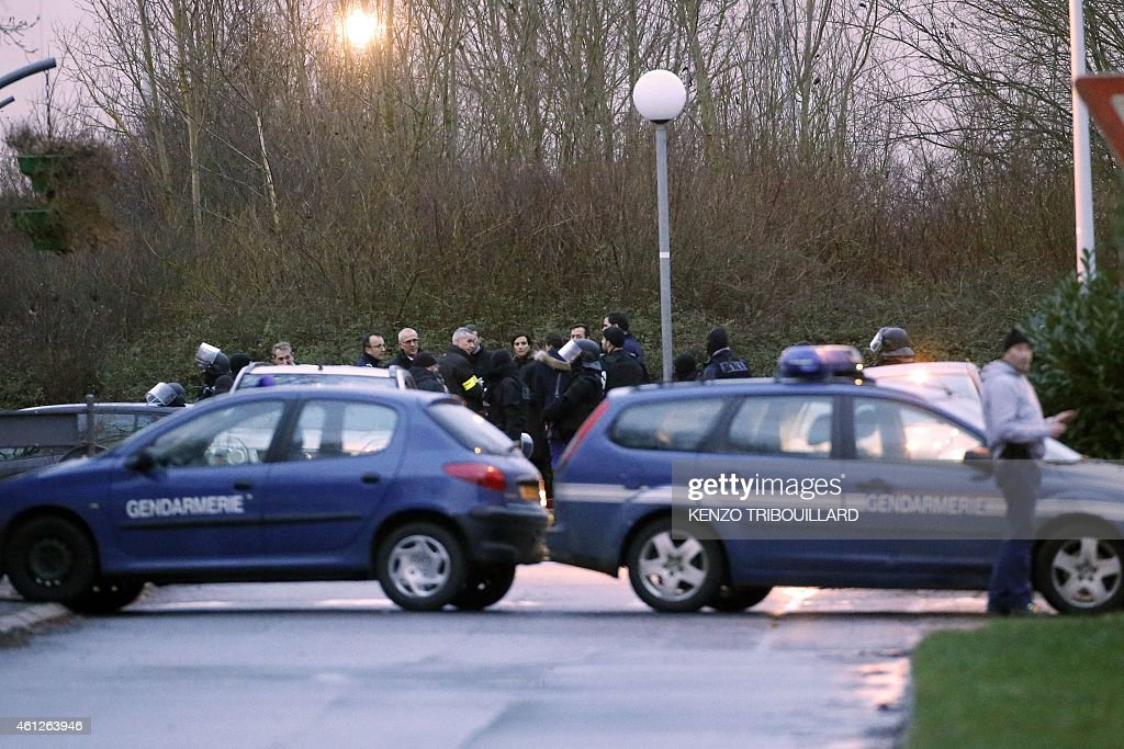 Paris' prosecutor Francois Molins (C, yellow armband) is surrounded by French gendarmes and firefighters in Dammartin-en-Goele, north-east of Paris, at the site where two brothers suspected of slaughtering 12 people in an Islamist attack on French satirical newspaper Charlie Hebdo held one person hostage as police cornered the gunmen, on January 9, 2015. Elite commando units on January 9 mounted an assault killing the two Islamist brothers suspected of carrying out the Charlie Hebdo massacre, as hostages in a second hostage drama were freed at a Jewish supermarket in eastern Paris. AFP PHOTO / KENZO TRIBOUILLARD