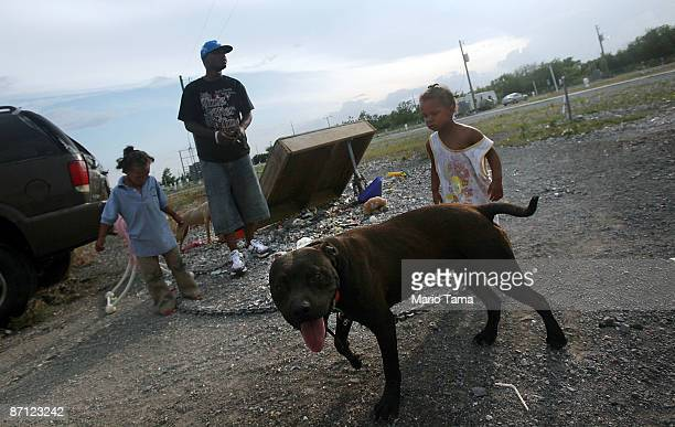 Paris Riley uncle Matthew Riley and China Barthelemy stand outside the FEMA trailer the children live in May 11 2009 in Port Sulphur Louisiana Seven...
