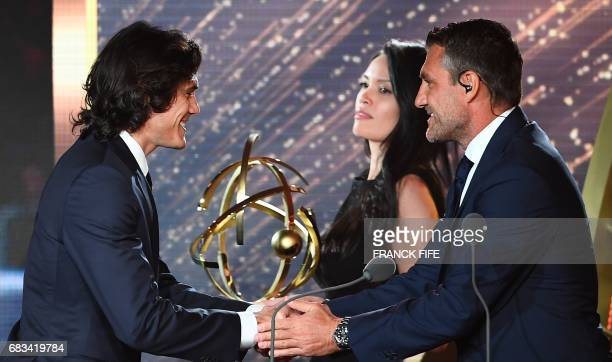 Paris Saint Germain forward Edinson Cavani receives the French players' Ligue 1 Player of the Year award from from former Italian player Cristian...