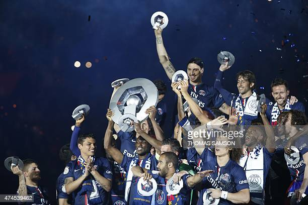 Paris Saint Germain players hold up the trophy following the French L1 football match between Paris SaintGermain vs Reims on May 23 2015 at the Parc...