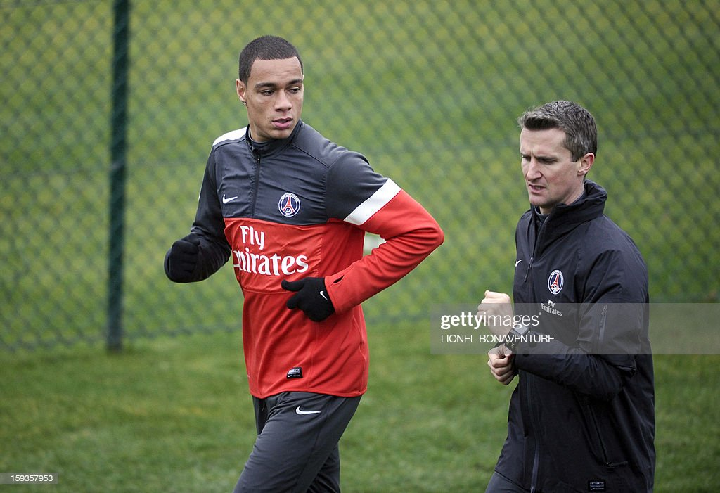 Paris Saint Germain's Dutch defender Gregory Van Der Wiel (L) takes part in a training session with a technical staff member, on January 10, 2013 at the Camp des Loges, the PSG football club training center in Saint-Germain-en-Laye, west of Paris.