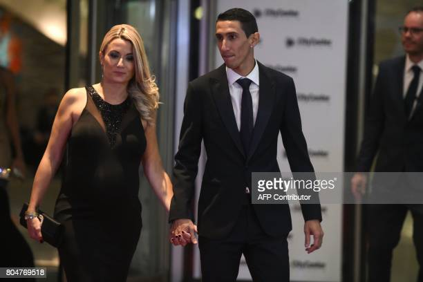Paris Saint Germain's footballer Argentine Angel di Maria poses with his wife on a red carpet during Argentine football star Lionel Messi and...