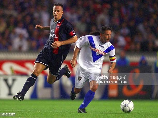 Paris Saint Germain's Frederic Dehu fights for the ball with Brescia's Roberto Baggio during the Intertoto finals first leg at the Parc des Princes...