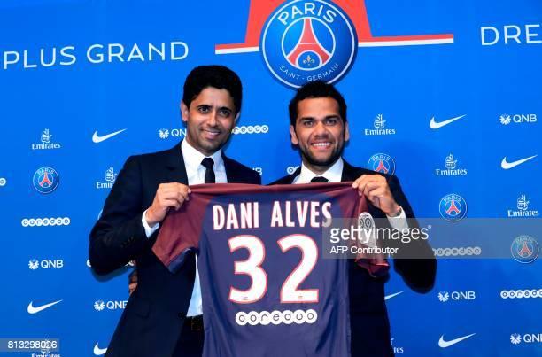 Paris Saint Germain's new Brazilian defender Dani Alves and PSG's Qatari president Nasser AlKhelaifi pose with Alves' jersey during a press...