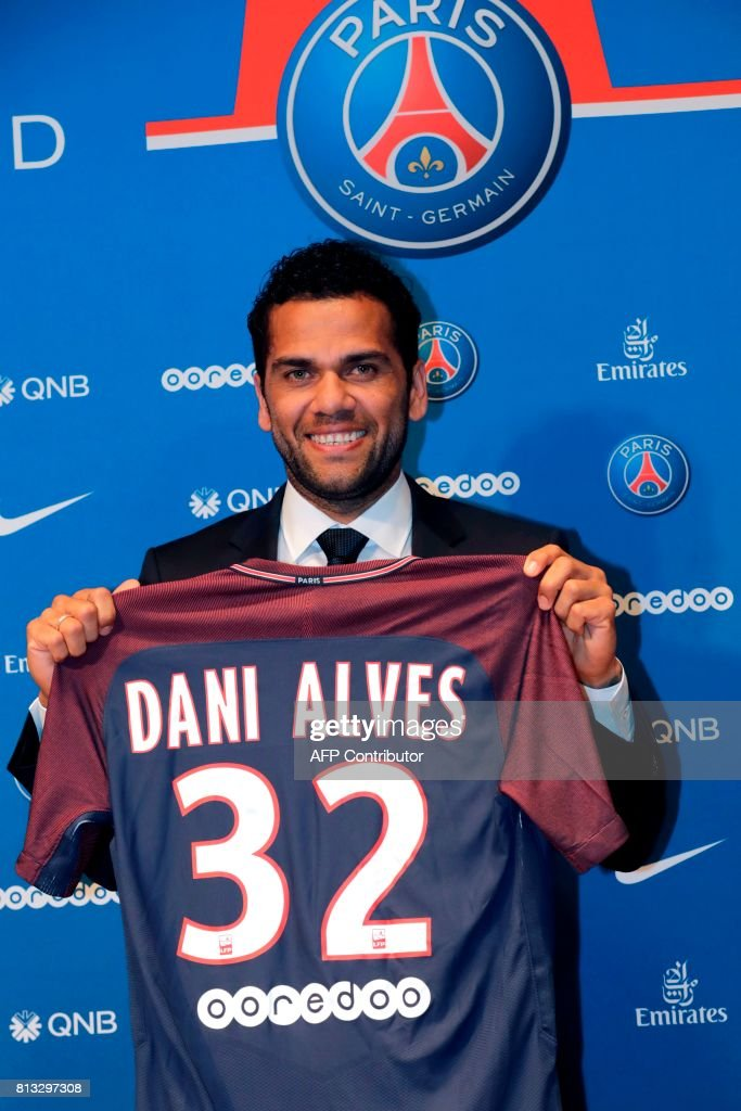Paris Saint Germain's (PSG) new Brazilian defender Dani Alves poses with his jersey as he gives a press conference on July 12, 2017, in Paris. Alves has signed a two-year deal with Paris Saint-Germain, the French club confirmed on July 12. / AFP PHOTO / Thomas Samson