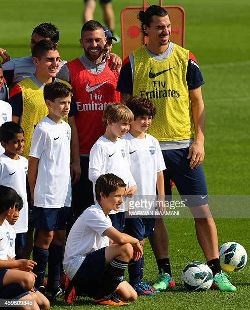 Paris SaintGermain football club's Zlatan Ibrahimovic and teammates pose for a picture with children of the Evolution football academy before a...