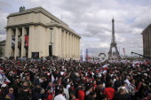 Paris SaintGermain French football team supporters celebrate and await the arrival of the PSG players for the winners parade after winning the French...