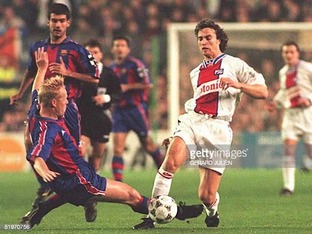 Paris SaintGermain striker David Ginola avoids the tackle of Barcelona's Ronald Koeman 01 March during their first leg Champions League quarterfinal...