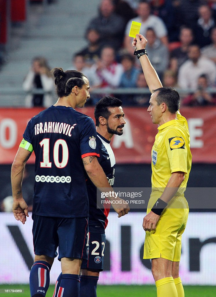 Paris Saint-Germain's Argentine forward Ezequiel Lavezzi (C) is given a yellow card by referee Ruddy Buquet during a French L1 football match between Valenciennes and Paris Saint-Germain on September 25, 2013 at the Stade du Hainaut in Valenciennes, northern France.
