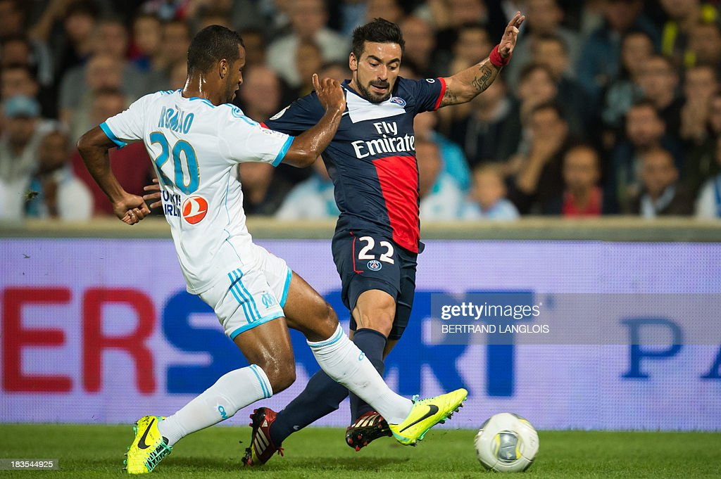 Paris Saint-Germain's Argentine forward Ezequiel Lavezzi (R) vies with Marseille's Togolese midfielder Jacques-Alaixys Romao (L) during the French L1 football match Olympique de Marseille vs Paris Saint-Germain on October 6, 2013 at the Velodrome stadium in Marseille, southern France. AFP PHOTO / BERTRAND LANGLOIS