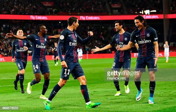 Paris SaintGermain's Argentinian forward Angel Di Maria and Paris SaintGermain's Uruguayan forward Edinson Cavani celebrate with teammates after...