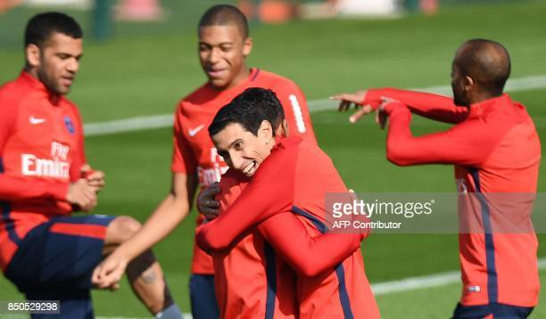 Paris SaintGermain's Argentinian forward Angel Di Maria jokes with teammates during a training session at the club's training center in...