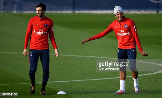 Paris SaintGermain's Argentinian forward Javier Pastore jokes with Paris SaintGermain's French forward Kylian MBappe during a training session on...