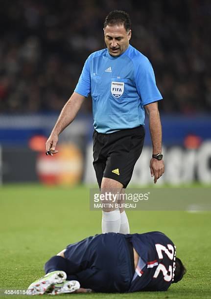 Paris SaintGermain's Argentinian midfielder Ezequiel Lacezzi lies on the ground as the referee walks during the UEFA Champions League group F...