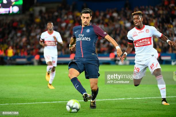 Paris SaintGermain's Argentinian midfielder Javier Pastore drives the ball next to Toulouse's Swiss defender Francois Moubandje during the French L1...