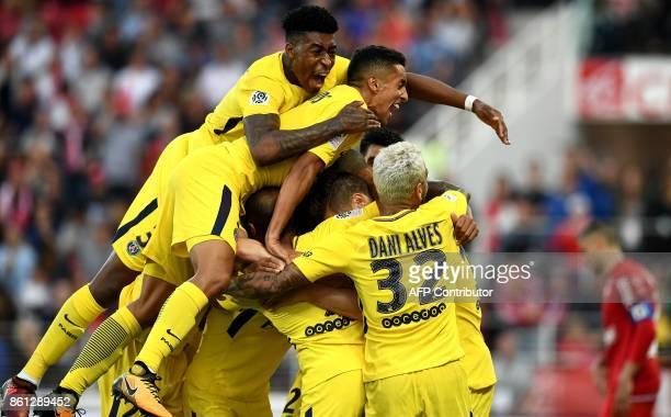 Paris SaintGermain's Belgian defender Thomas Meunier celebrates scoring a goal with teammates during the French L1 football match between Dijon and...