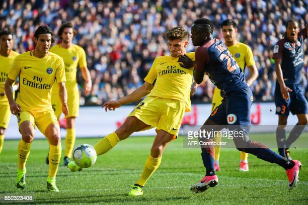 Paris SaintGermain's Belgian defender Thomas Meunier clears a ball under pressure from Montpellier's Chadian forward Casimir Ninga during the French...