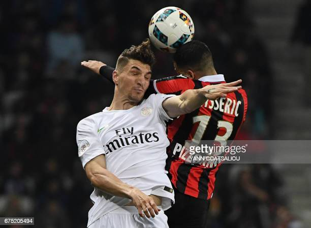 Paris SaintGermain's Belgium defender Thomas Meunier jumps to head the ball with Nice's French midfielder Valentin Eysseric during the French L1...