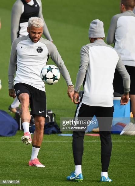 Paris SaintGermain's Brazilian defender Dani Alves controls the ball next to Paris SaintGermain's Brazilian forward Neymar as they take part in a...