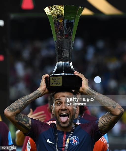 TOPSHOT Paris SaintGermain's Brazilian defender Dani Alves holds the trophy as he celebrates with teammates after winning the French Trophy of...