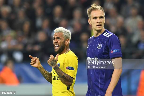 Paris SaintGermain's Brazilian defender Dani Alves reacts next to Anderlecht's Polish forward Lukasz Teodorczyk during the UEFA Champions League...