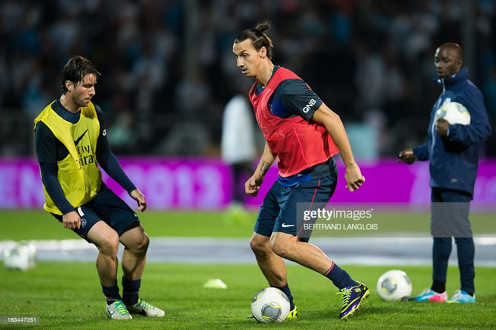 Paris Saint-Germain's Brazilian defender Maxwell and Swedish forward Zlatan Ibrahimovic (C) warm up before the French L1 football match Olympique de Marseille (OM) vs Paris Saint-Germain (PSG) on October 6, 2013 at the Velodrome stadium in Marseille, southern France.