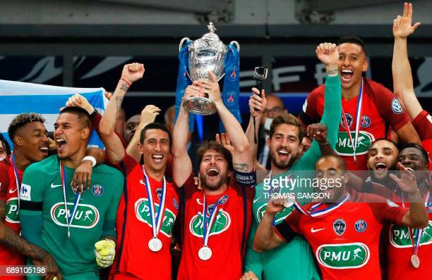 TOPSHOT Paris SaintGermain's Brazilian defender Maxwell holds the trophy as he celebrates winning the French Cup final football match between Paris...
