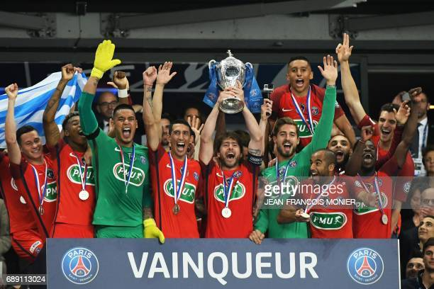 Paris SaintGermain's Brazilian defender Maxwell holds the trophy as he celebrates with teammate after winning the French Cup final football match...