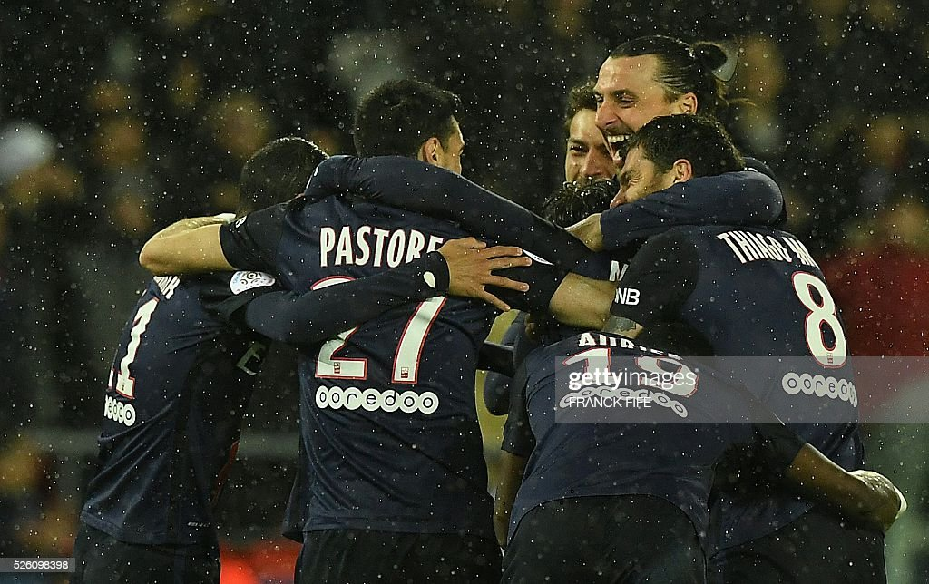 Paris Saint-Germain's Brazilian defender Maxwell (hidden) is congratulated by teammates after scoring a goal during the French L1 football match between Paris Saint-Germain and Rennes at the Parc des Princes stadium in Paris on April 30, 2016. / AFP / FRANCK