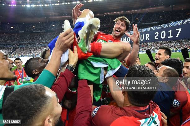 TOPSHOT Paris SaintGermain's Brazilian defender Maxwell is lifted by teammates after winning the French Cup final football match between Paris...