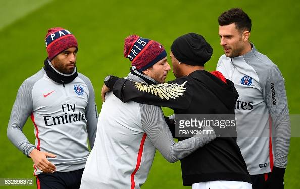 Paris SaintGermain's Brazilian defender Maxwell shakes hands with former Brazilian football player Ronaldinho before a training session on January 28...