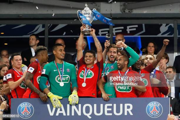 TOPSHOT Paris SaintGermain's Brazilian defender Thiago Silva celebrates with the trophy after winning the French Cup final football match between...