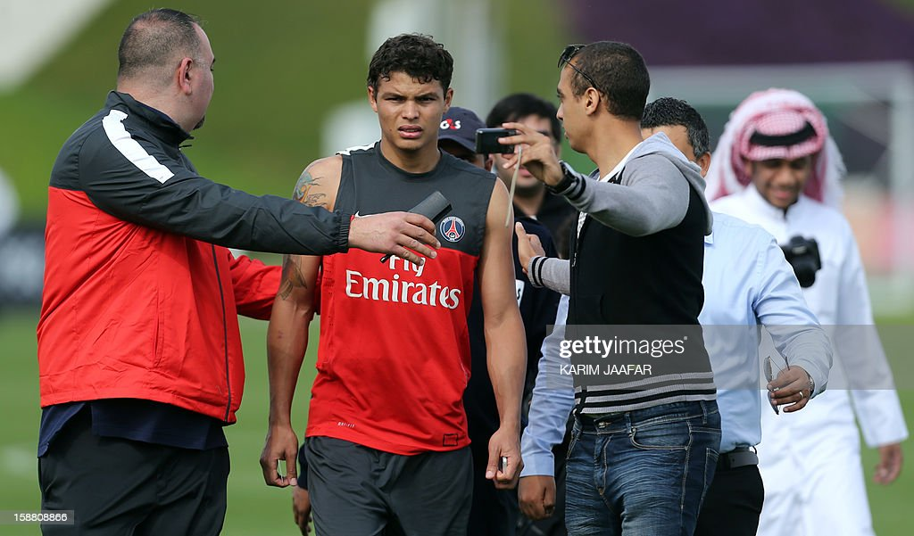 Paris Saint-Germain's (PSG) Brazilian defender Thiago Silva (C) has his picture taken by a fan following a training session at the Aspire Academy of Sports Excellence in the Qatari capital Doha on December 30, 2012. PSG is in Qatar for a week-long training camp before the resumption of the French Ligue 1 after the winter break.