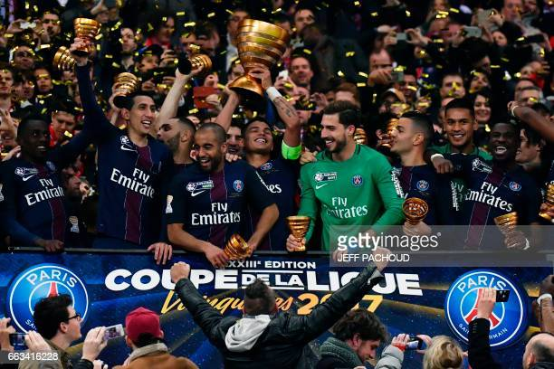 Paris SaintGermain's Brazilian defender Thiago Silva holds the trophy as he celebrates with teammates after winning the French League Cup final...