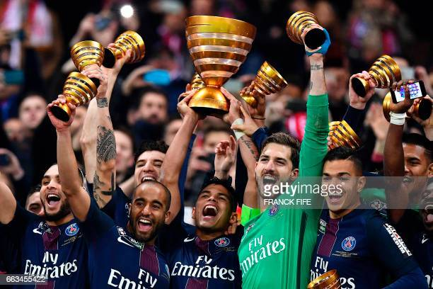 TOPSHOT Paris SaintGermain's Brazilian defender Thiago Silva holds the trophy as he celebrates with teammates after winning the French League Cup...