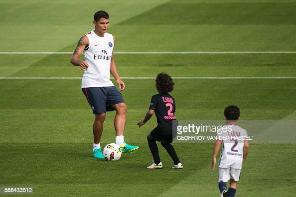 Paris SaintGermain's Brazilian defender Thiago Silva plays with his children as he takes part in a training session at the Camp des Loges training...