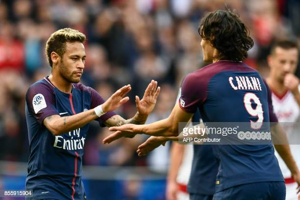 Paris SaintGermain's Brazilian forward Neymar and Paris SaintGermain's Uruguayan forward Edinson Cavani celebrate after Neymar scored a penalty kick...