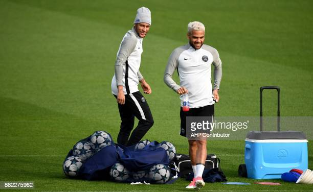 Paris SaintGermain's Brazilian forward Neymar and Paris SaintGermain's Brazilian defender Dani Alves react during a training session on October 17...