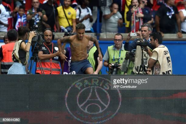 Paris SaintGermain's Brazilian forward Neymar comes back in the football field after giving away is new team jersey to supporters during his...