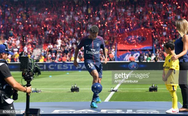 Paris SaintGermain's Brazilian forward Neymar controls the ball on stage during his presentation to the fans at the Parc des Princes stadium in Paris...