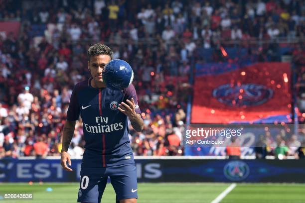 Paris SaintGermain's Brazilian forward Neymar eyes the ball as he performs with it on stage during his presentation to the fans at the Parc des...
