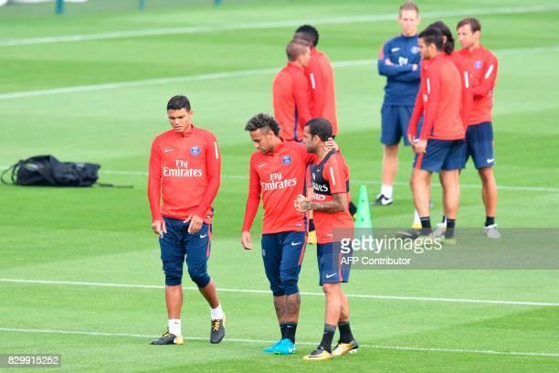 Paris SaintGermain's Brazilian forward Neymar flanked by Paris SaintGermain's Brazilian defender Thiago Silva and Paris SaintGermain's Brazilian...