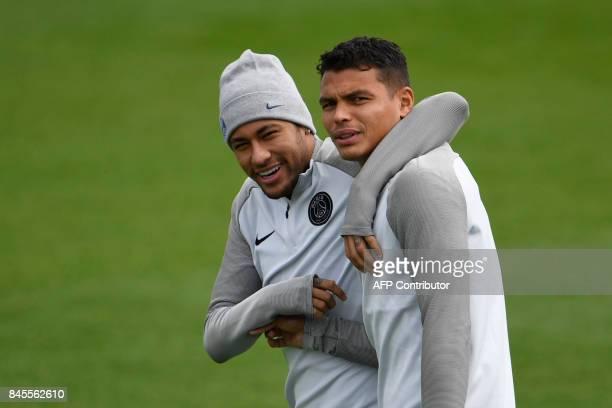 TOPSHOT Paris SaintGermain's Brazilian forward Neymar hugs Paris SaintGermain's Brazilian defender Thiago Silva during a training session at the Camp...